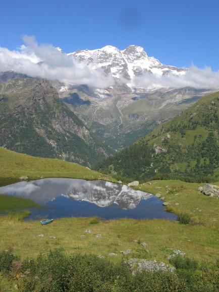 Il suggestivo laghetto dell'alpe Campo che rispecchia il versante e la parete sud-est del monte Rosa