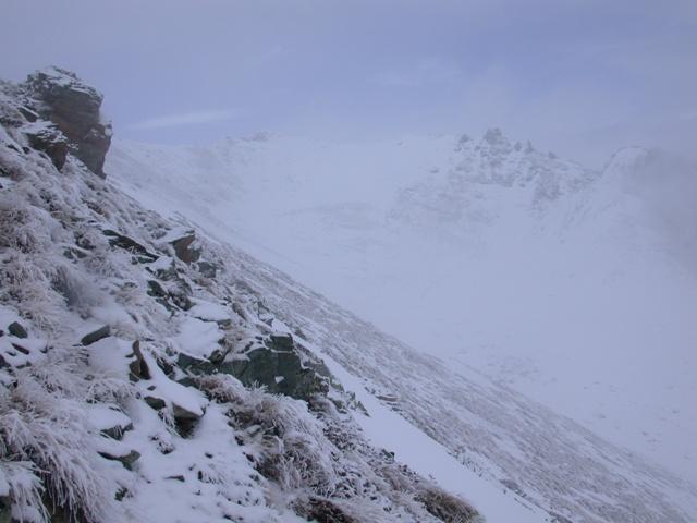 Sulla sinistra il pendio pericoloso sotto la cima (ora privo di neve). Al centro della foto il colle.