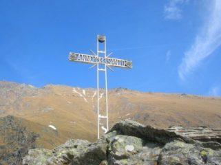 La croce presente sul roccione sopra il santuario. Sullo sfondo il Colle della Borra