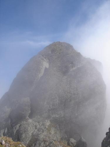 L'anticima dalla cresta occidentale. La pareta si supera con il Caminetto, una cengia e facili roccette (corde fisse).