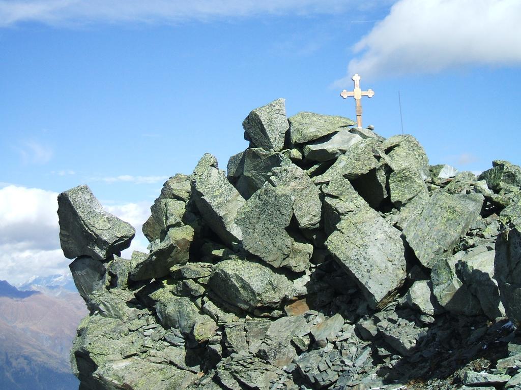 La croce di vetta ed il masso che sfida la legge dell'equilibrio