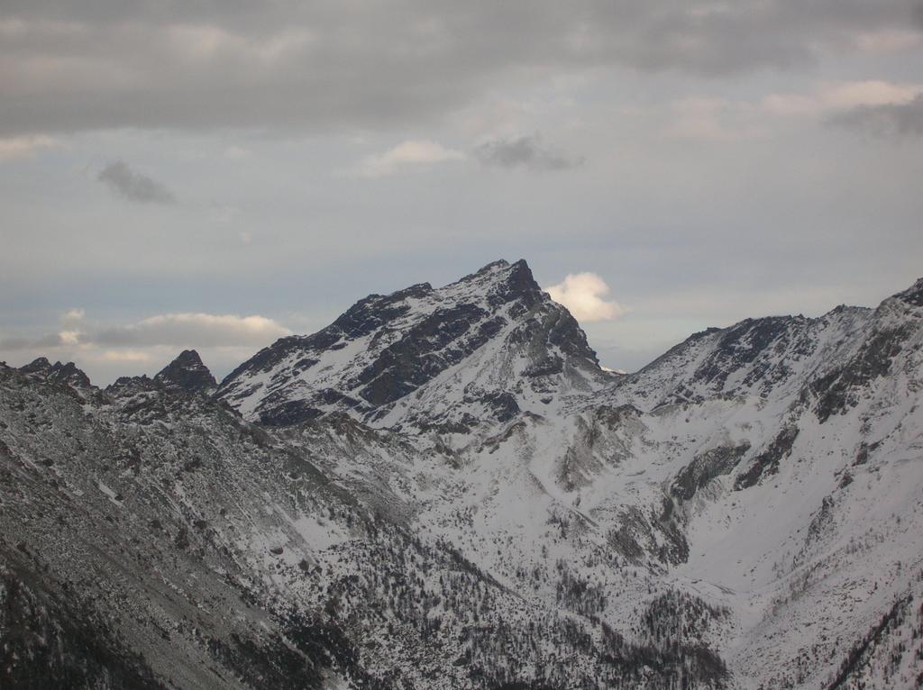 Il versante nord-ovest del Mont Ruvi dal Mont Courquet. Spiccano nettamente i due canalini che permettono di superare la fascia rocciosa diagonale che scende verso nord dalla cresta sud.
