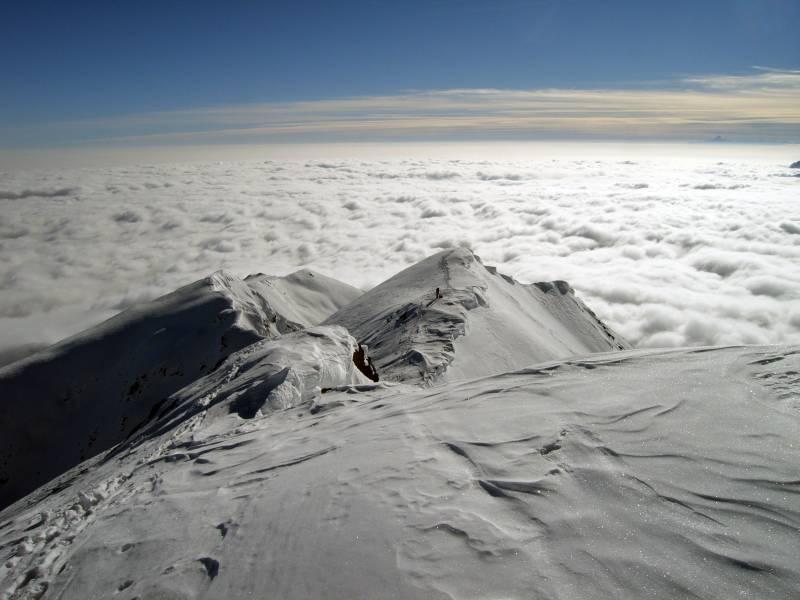 Dalla cima, sguardo verso la punta Cavalcurt e la pianura immersa nella nebbia