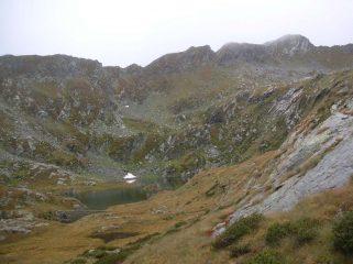 Il lago Chiletto. In alto a destra l' edificio sommitale del M.te Snatanel con, sulla sinistra, il canale erboso che consente di raggiungere la cima.