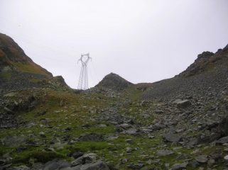 Il valloncello che dal versante di Piamprato sale al Col Santana sul quale sorge l'evidente traliccio dell' eletrodotto.
