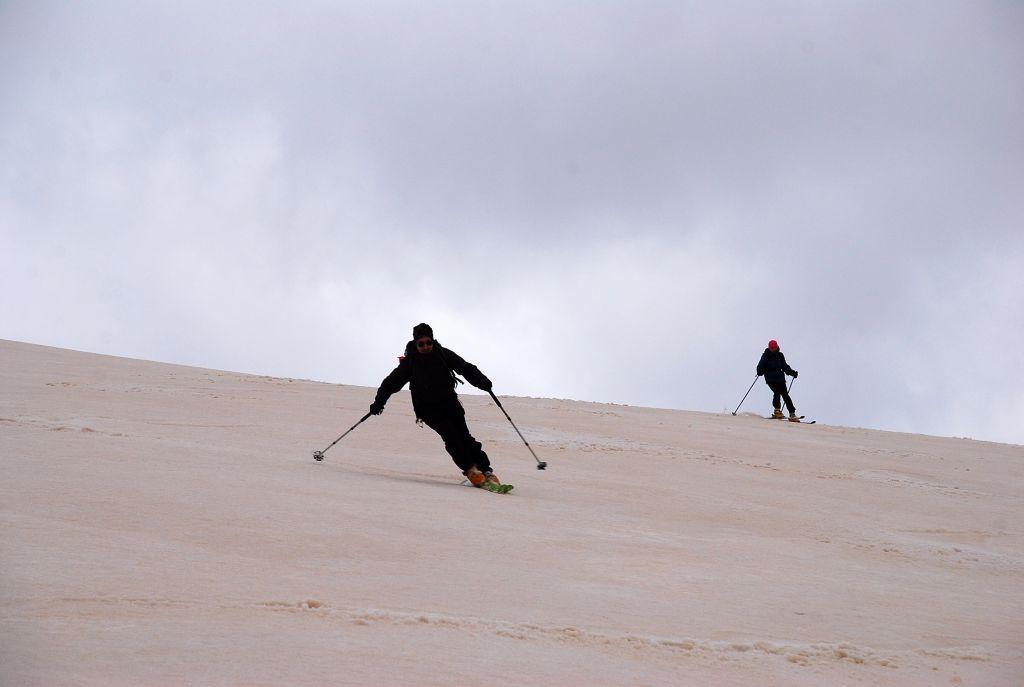 in discesa sull' ampio costone, con la neve colorata dalla terra riportata dal vento