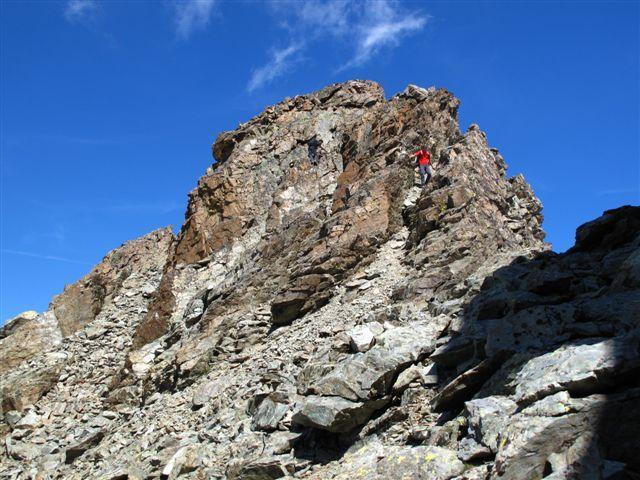 Dall'insellatura vista verso la punta Michelis: salita arrampicando dove ci sono le due persone o nel canale di pietre a sinistra dove si può camminare tra pietre instabili