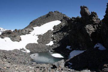 il minuscolo laghetto ghiacciato sotto la cima