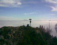 Cima, zaino e nubi sullo sfondo