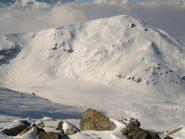 Dalla vetta, a Nord-Ovest si vede la Testa di Cervetto (2347 m), sopra i Laghi Luset, coperti di neve