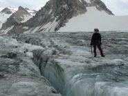 Roberto vicino ad un crepaccio con dietro il ghiacciaio risalito