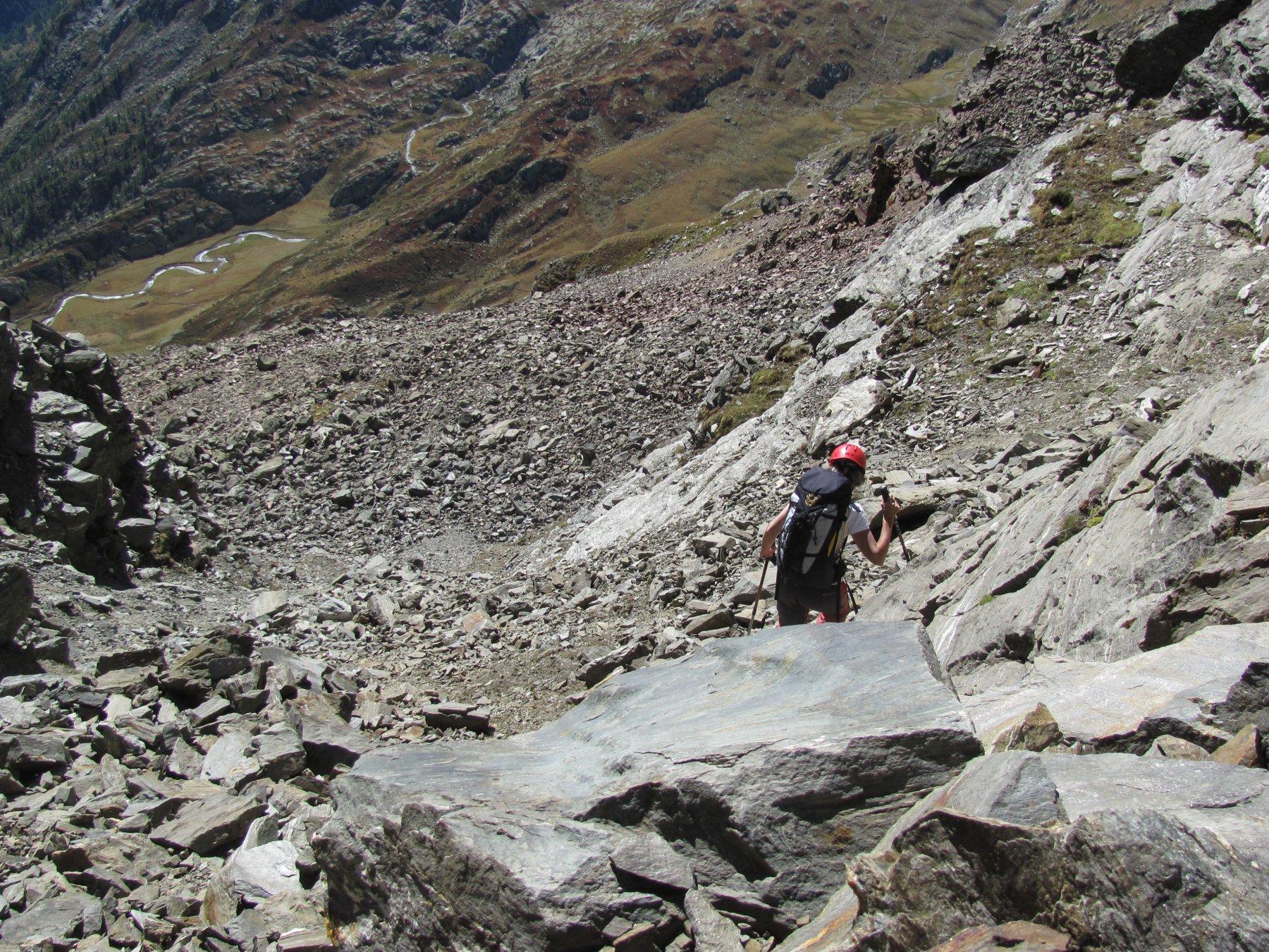 Insidiosi detriti sotto il Colle, in discesa. Il sentiero del ritorno è lungo il torrente che si vede al fondo.