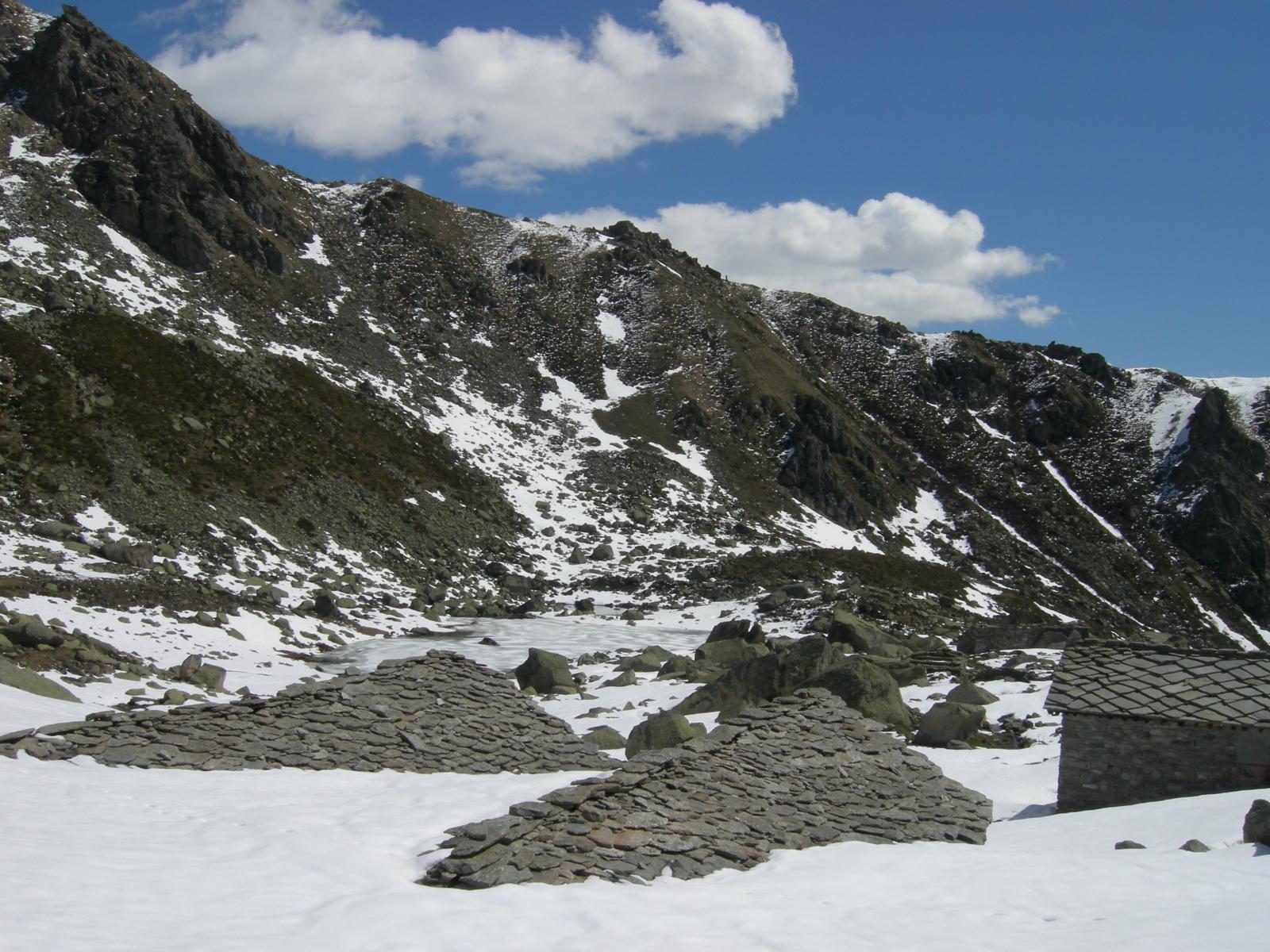 Baite immerse nella neve al Gias dei laghi. Sullo sfondo il lago inferiore