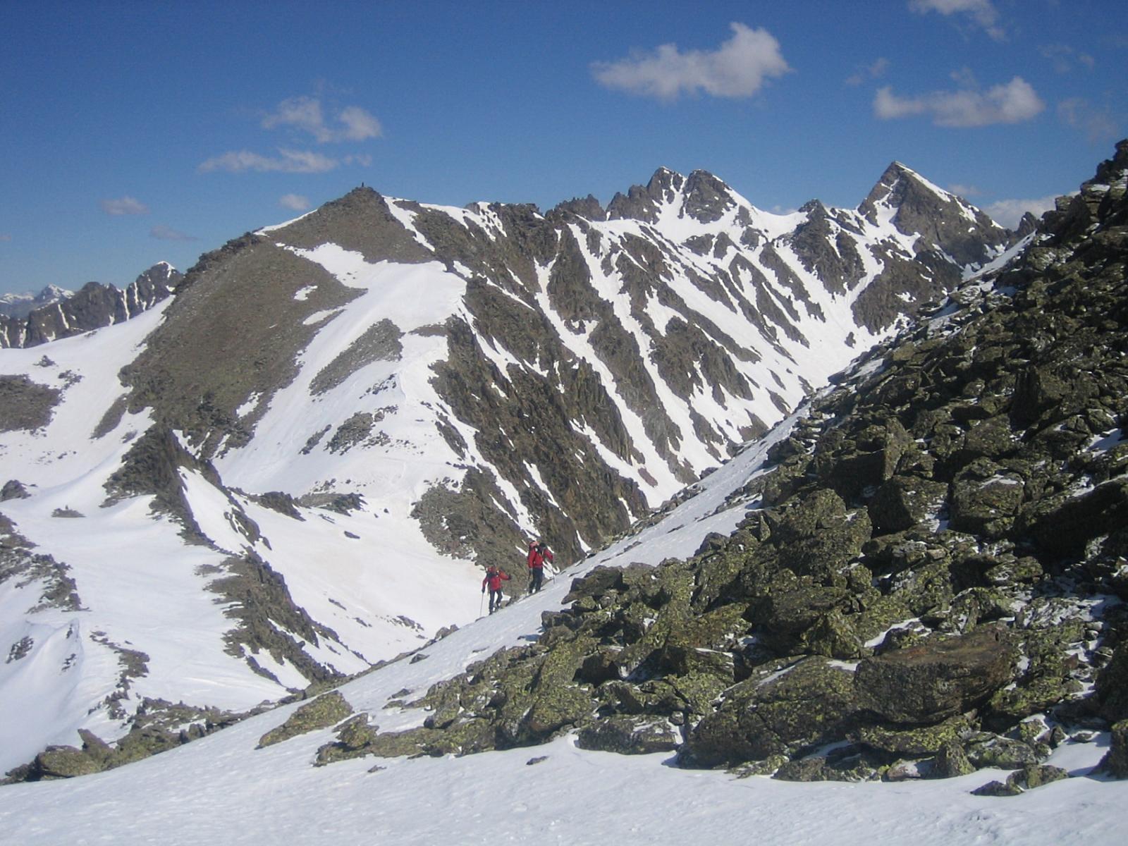 aggirato il  pietroso pendio sulla sinistra si sale con gli sci a pochi metri dalla cima; sulla destra la Cima del Corborant;