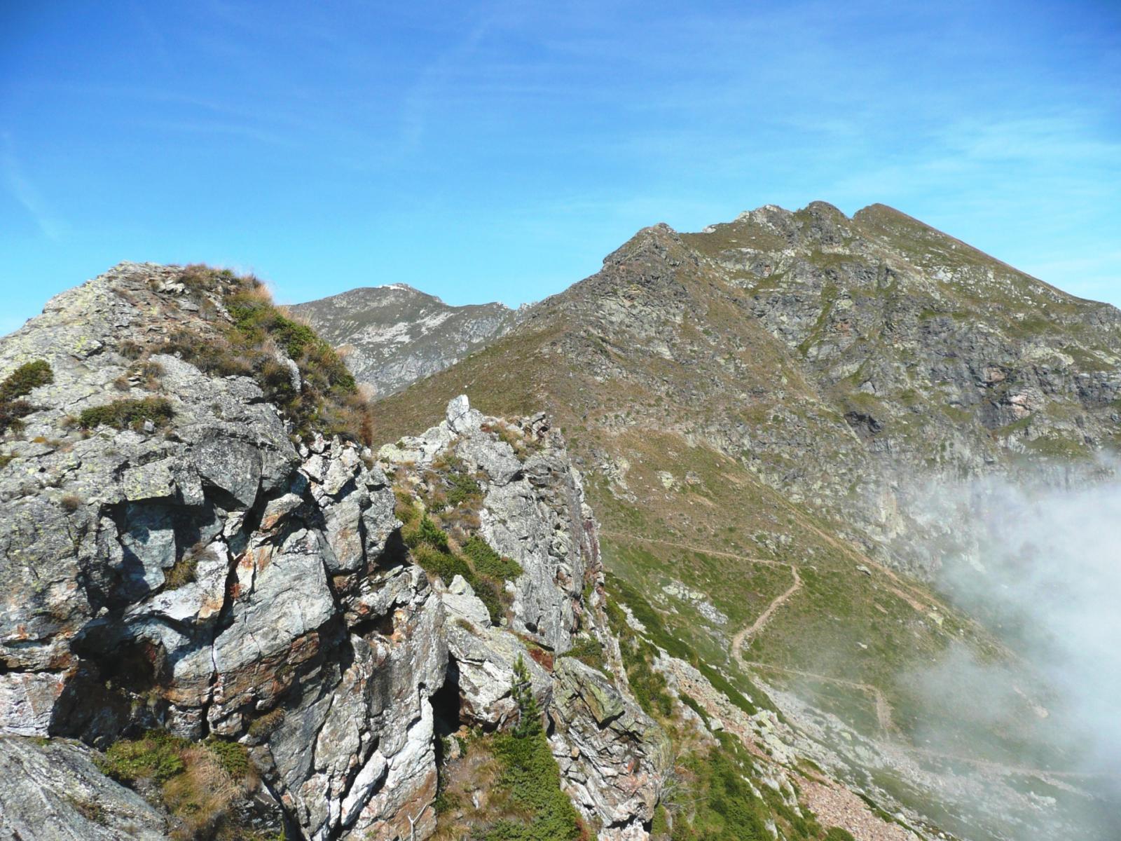 gli ultimi tornanti del Colle della Gragliasca, la Punta Gragliasca, la Pietra Bianca ed in primo piano i caratteristici torrioni calcarei della cresta