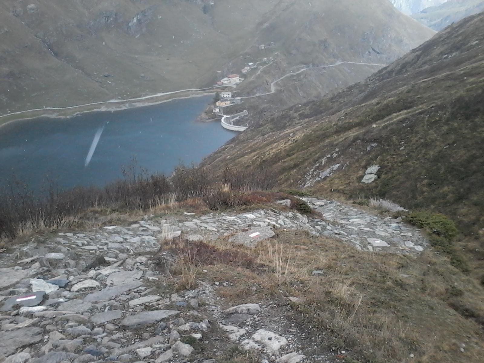 Massicciata e tornanti della carrellabile tipo 'D'; sullo sfondo diga e lago di Malciaussia.