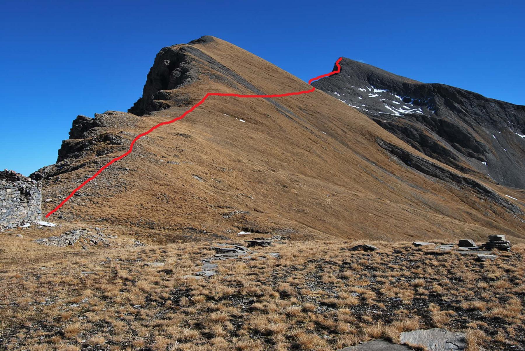 La meta vista dal Colle e la via di salita. Non visibili i canaloni tra il pendio erboso ed i colletti sotto la vetta