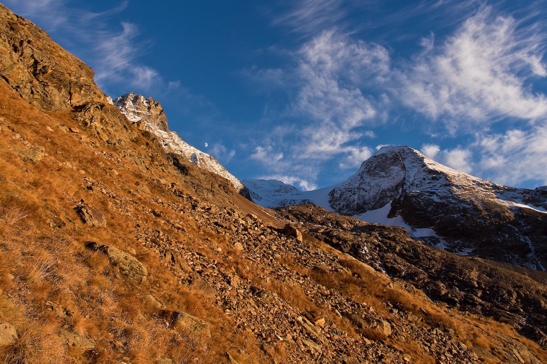 Sopra l'Alpe Bellatsa il tramonto tinge d'oro la Tour du Creton e lo Chateau des Dames