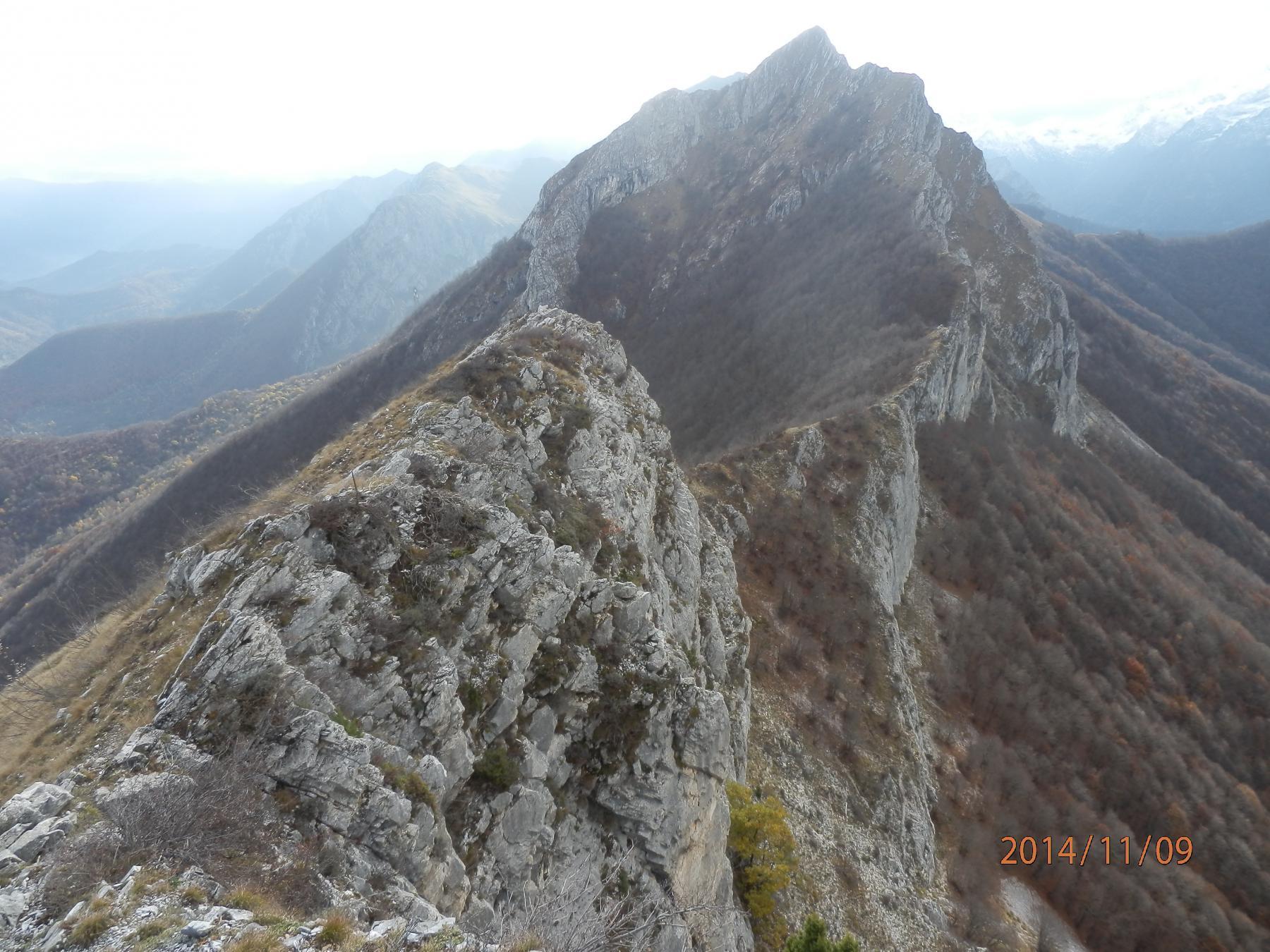 5- lungo la cresta...., in centro il Passo e sullo sfondo le Rocce della Scregna