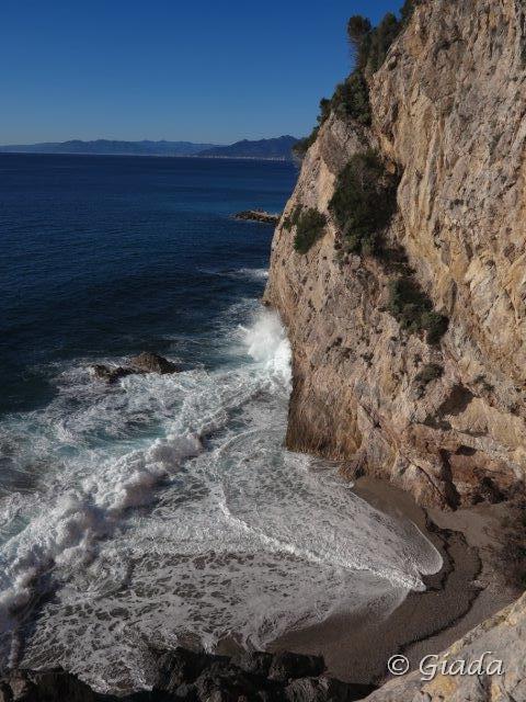 La spiaggia dei nudisti e le onde che si infrangono sulla falesia