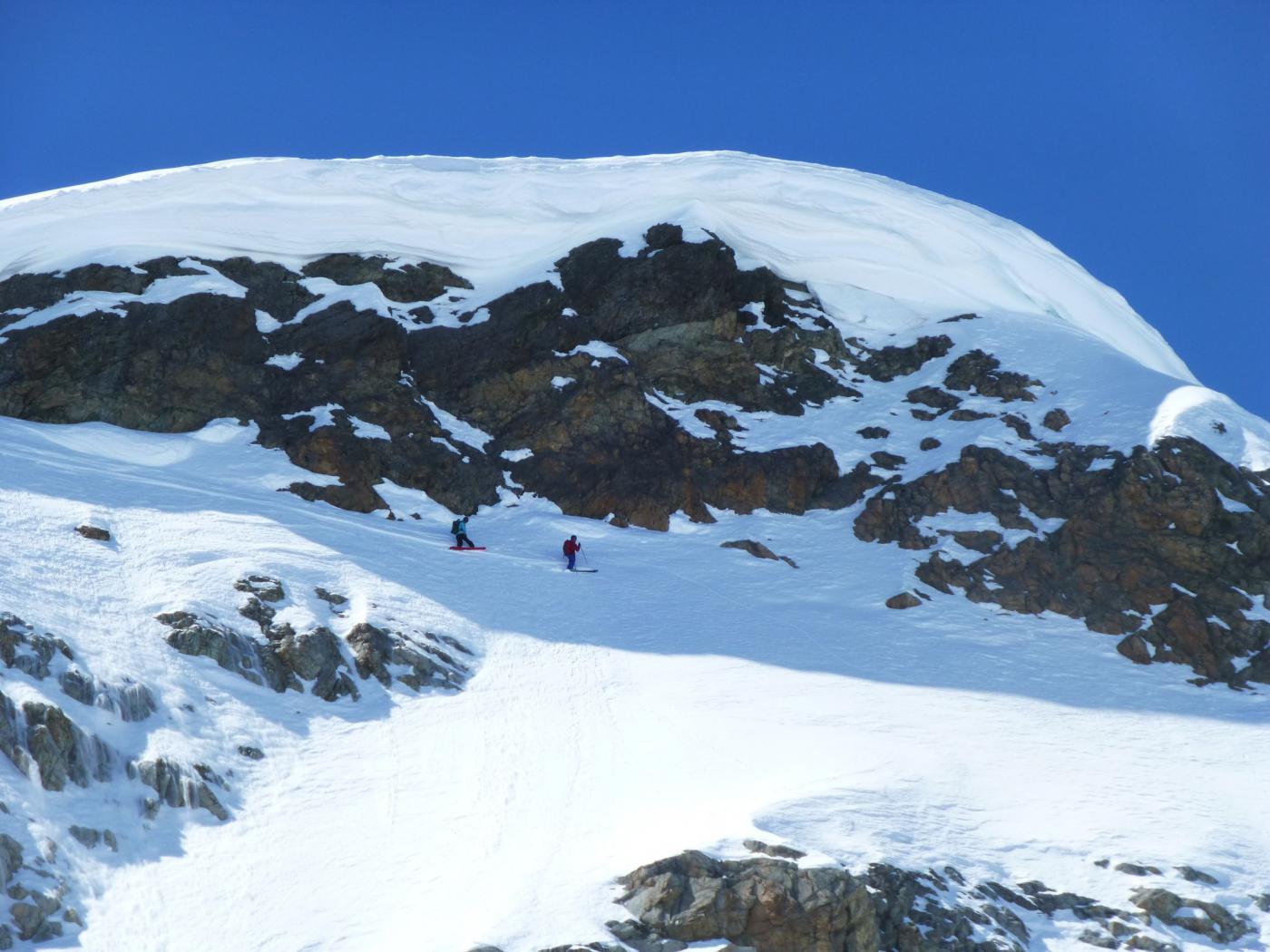 uno sciatore e uno snowboarder tagliano sotto le cornici e scenderanno poi diretti