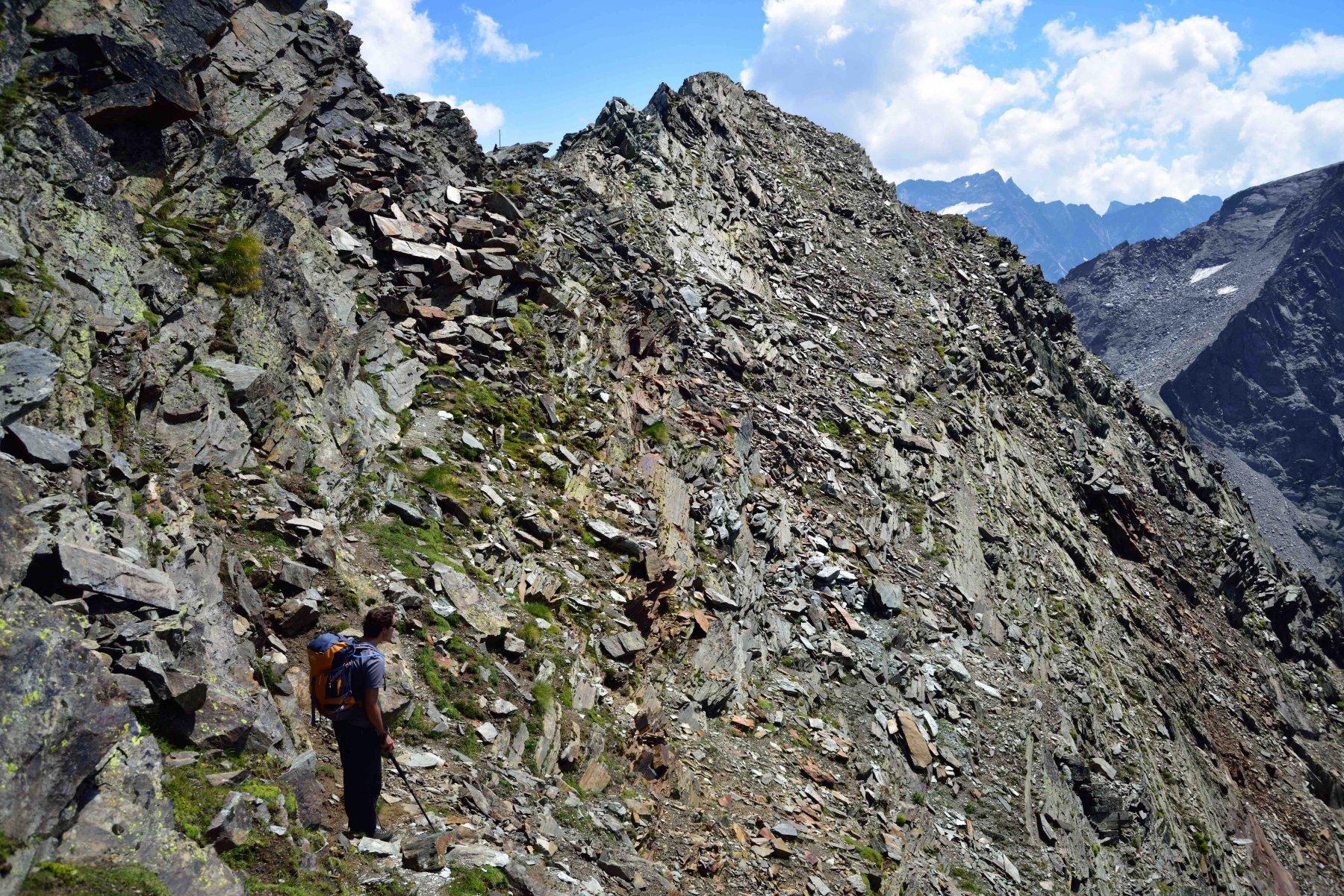 La cengia detritica in versante Valnontey. Un palo segnala il colletto sulla cresta.