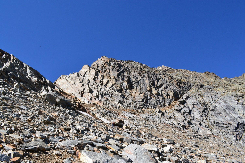 in salita sulla pietraia, a destra la cengia di accesso alla cresta