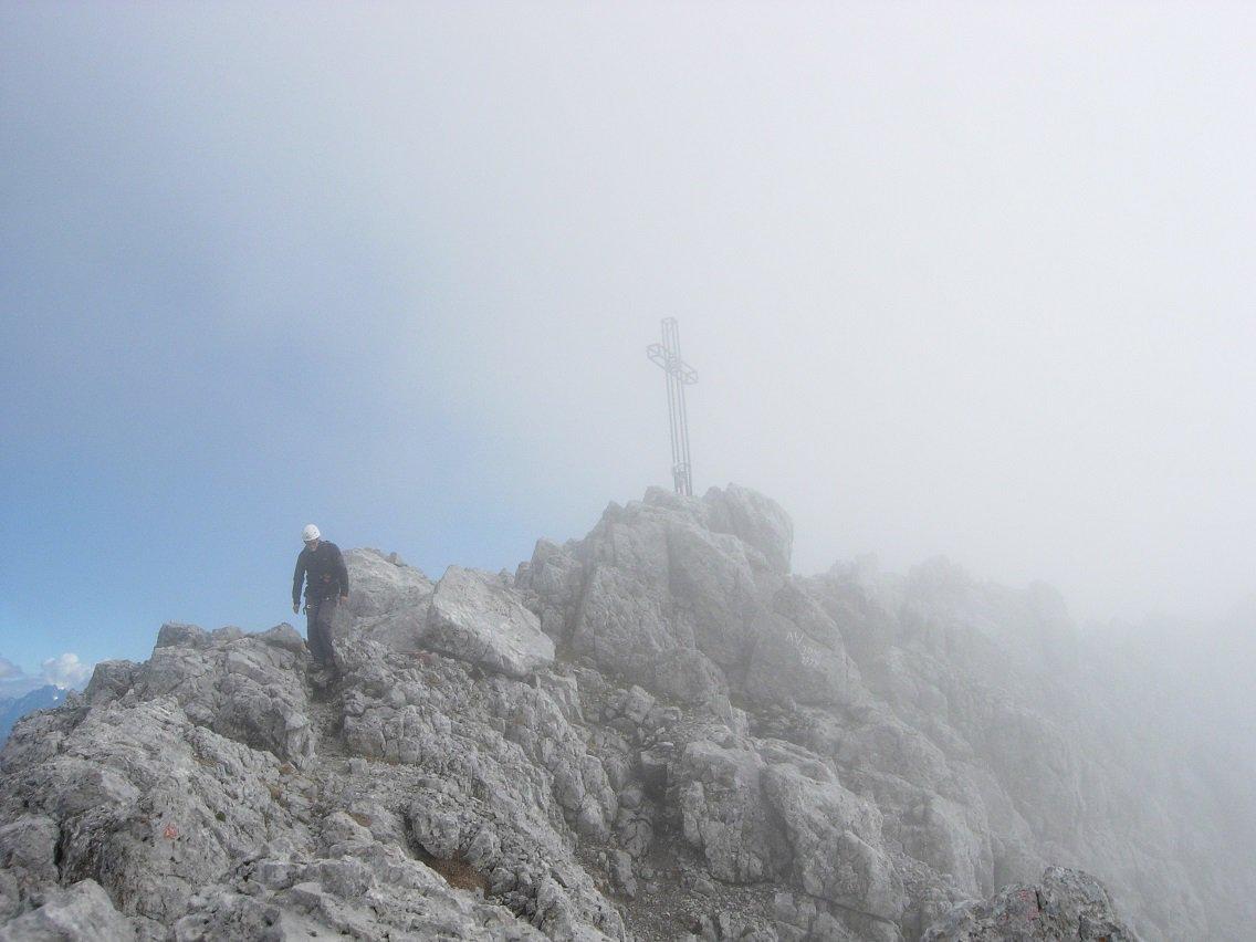 La croce di vetta tra sole  e nebbia