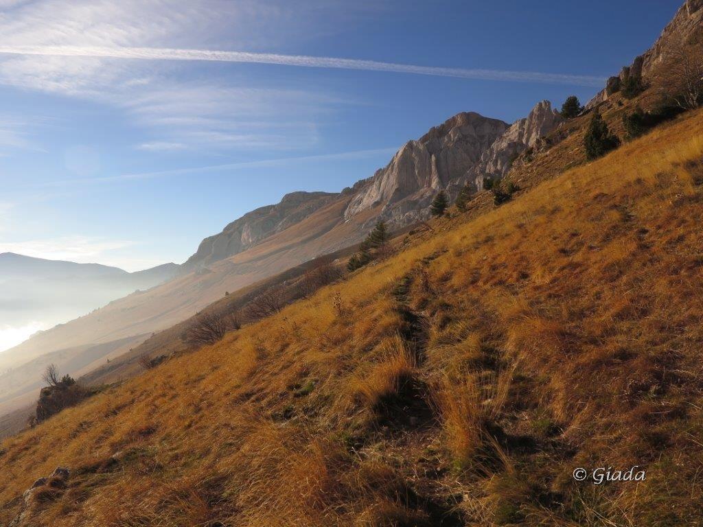 Sul sentiero del ritorno le Rocche del Manco e Pian Comune nella calda luce del tardo pomeriggio
