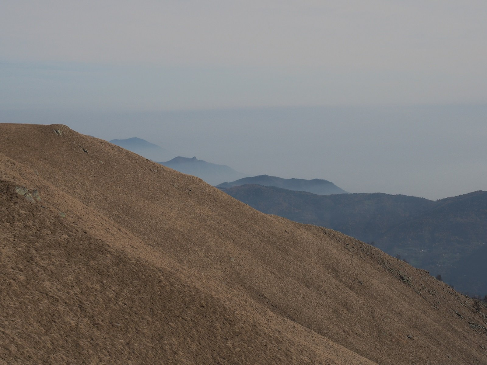 Ampi pendii erbosi lungo la dorsale di salita, con foschia fitta verso la pianura.