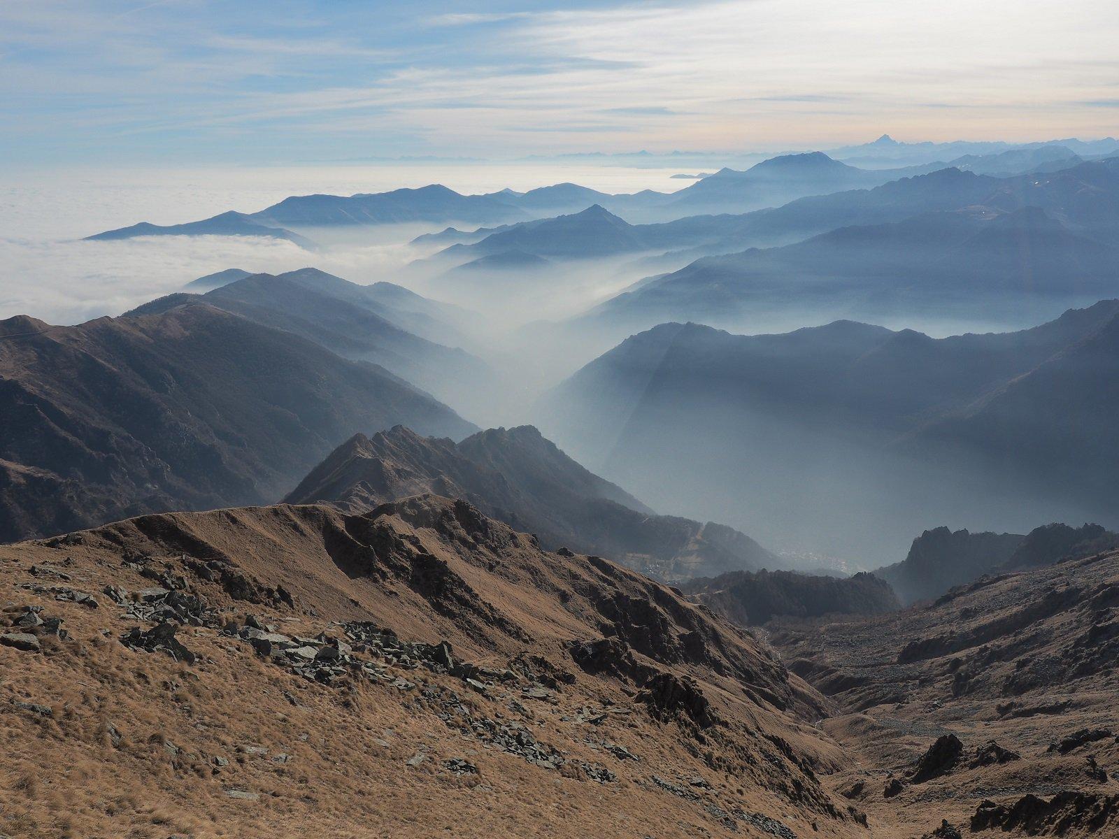 Uno sguardo verso sud dalla vetta, con foschia nelle valli e nebbia in pianura