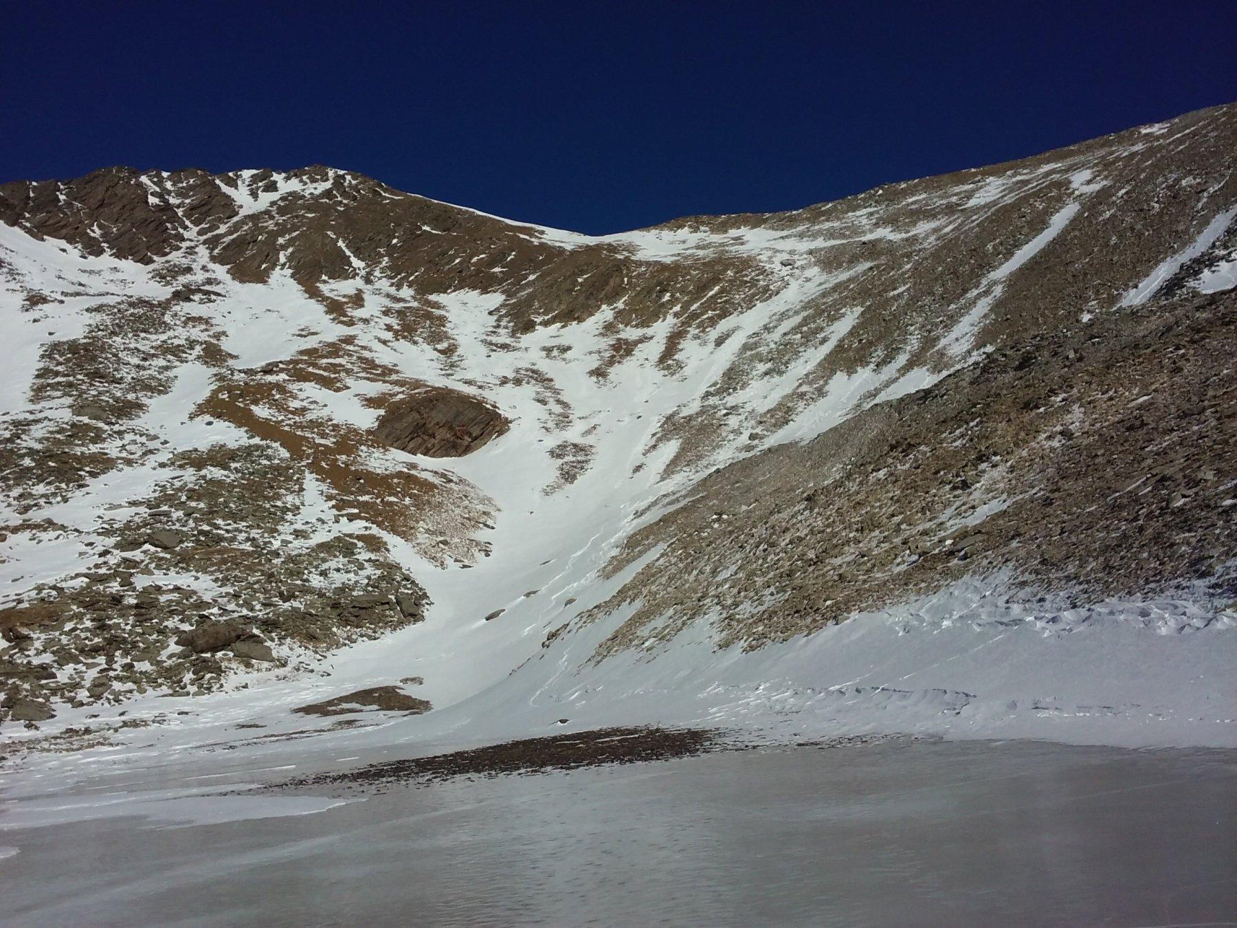 Lo scivolo nevoso sul fianco Sud della cima, visto dal lago Reisassa.