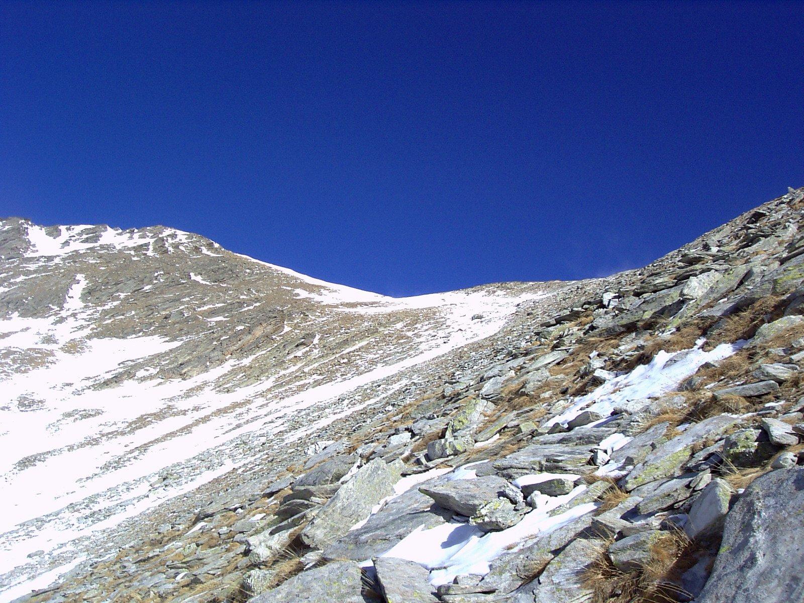Da poco sopra il lago Reisassa, la pietraia del fianco della cresta Sud con il colletto e la cima (foto A. Valfrè).