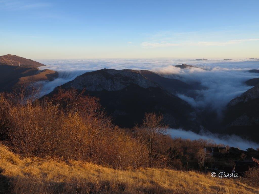 Il mare di soffici nuvole verso la Liguria nella calda luce che precede il tramonto debordano dalla diga montuosa