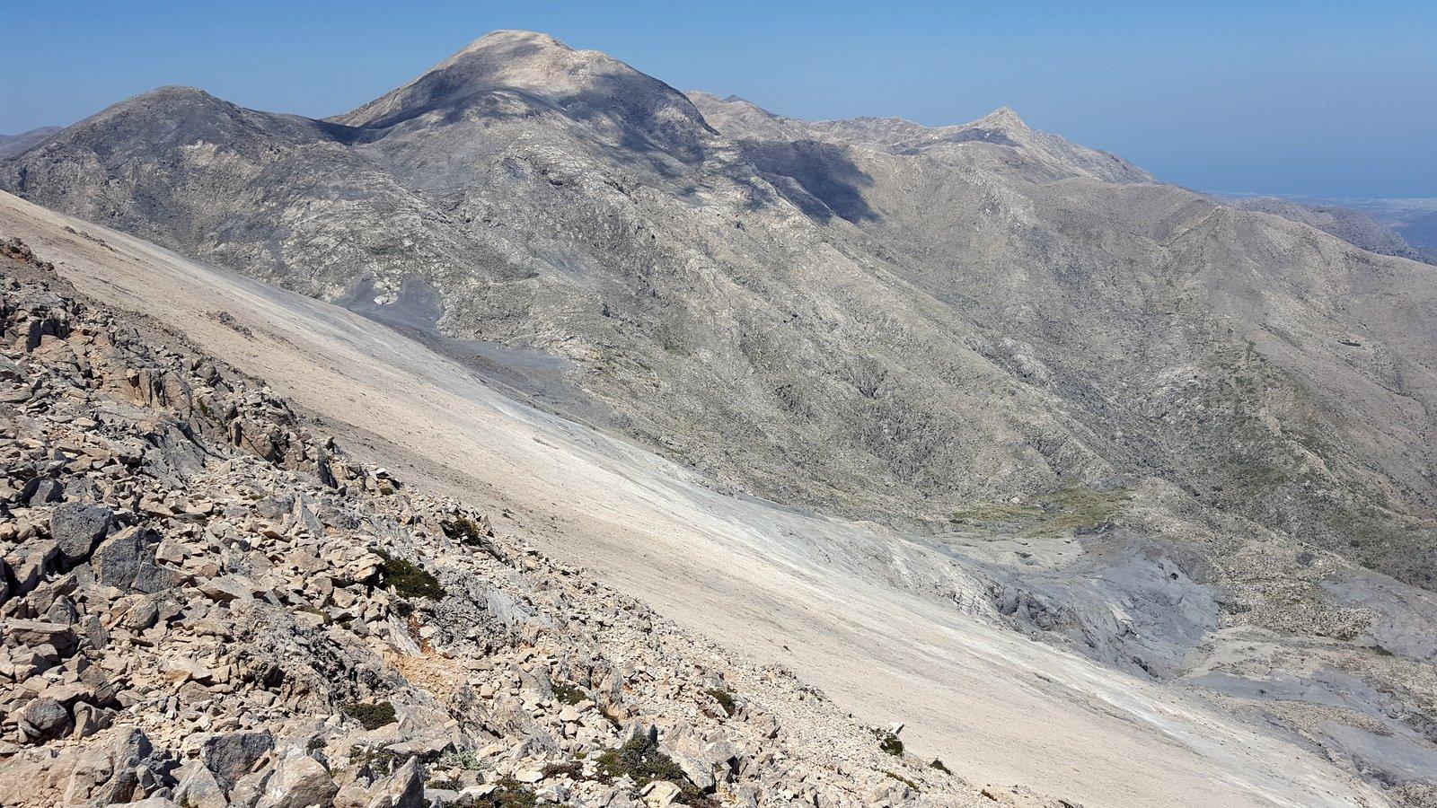 Gli impressionanti pendii di ghiaioni ai lati del tratto finale della cresta, sullo sfondo Aghio Pnevma