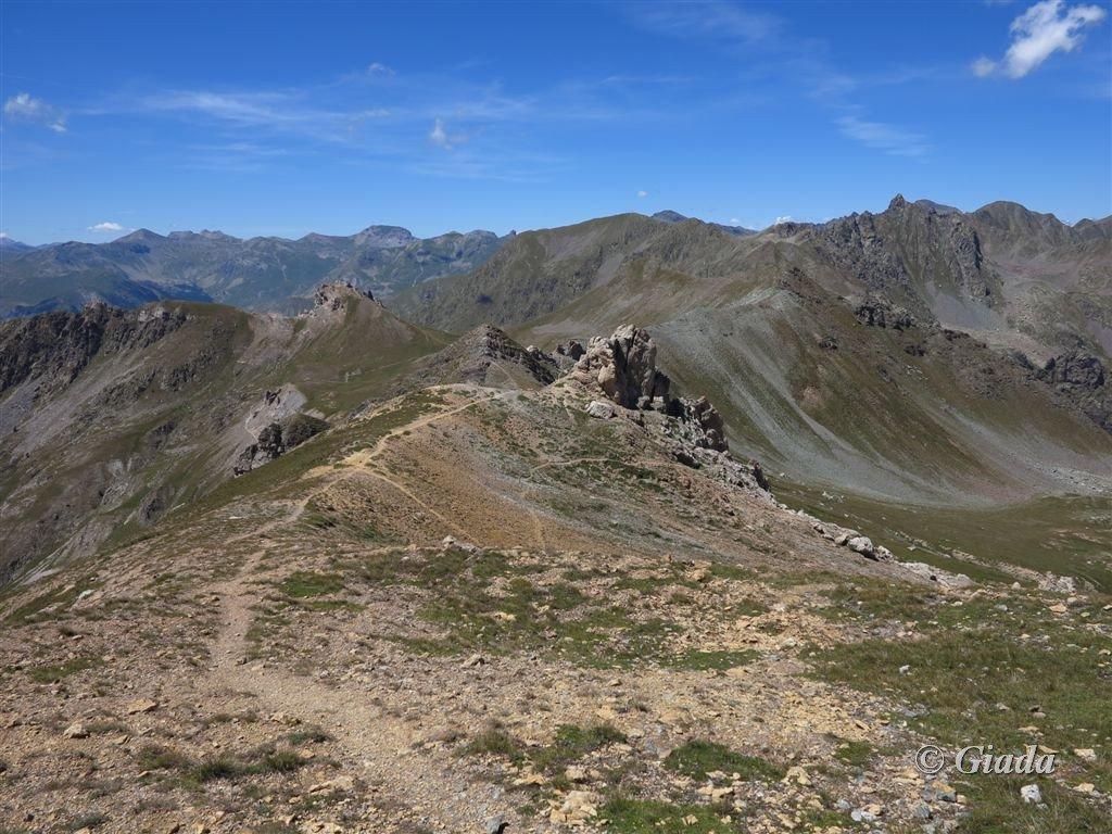 Il percorso sul panoramico crinale con la Aiguilles de Tortisse e la Cima Fer, a sx e a dx al centro della foto