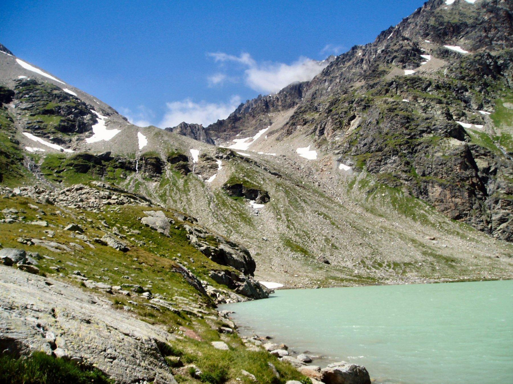 Lago con il pendio che sale al Col Sachere.