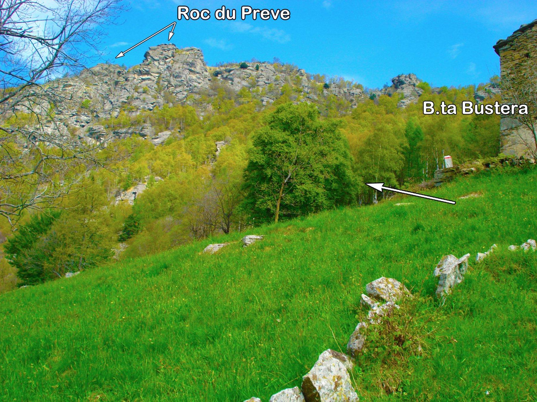Superata B.ta Bustera, prendere a sx il sentiero indicato con cartelli rossi-bianchi che inoltrandosi nel bosco, supera con una serie di tornanti una zona di imponenti massi posta più in alto per poi proseguire a sx fino alla base delle pareti