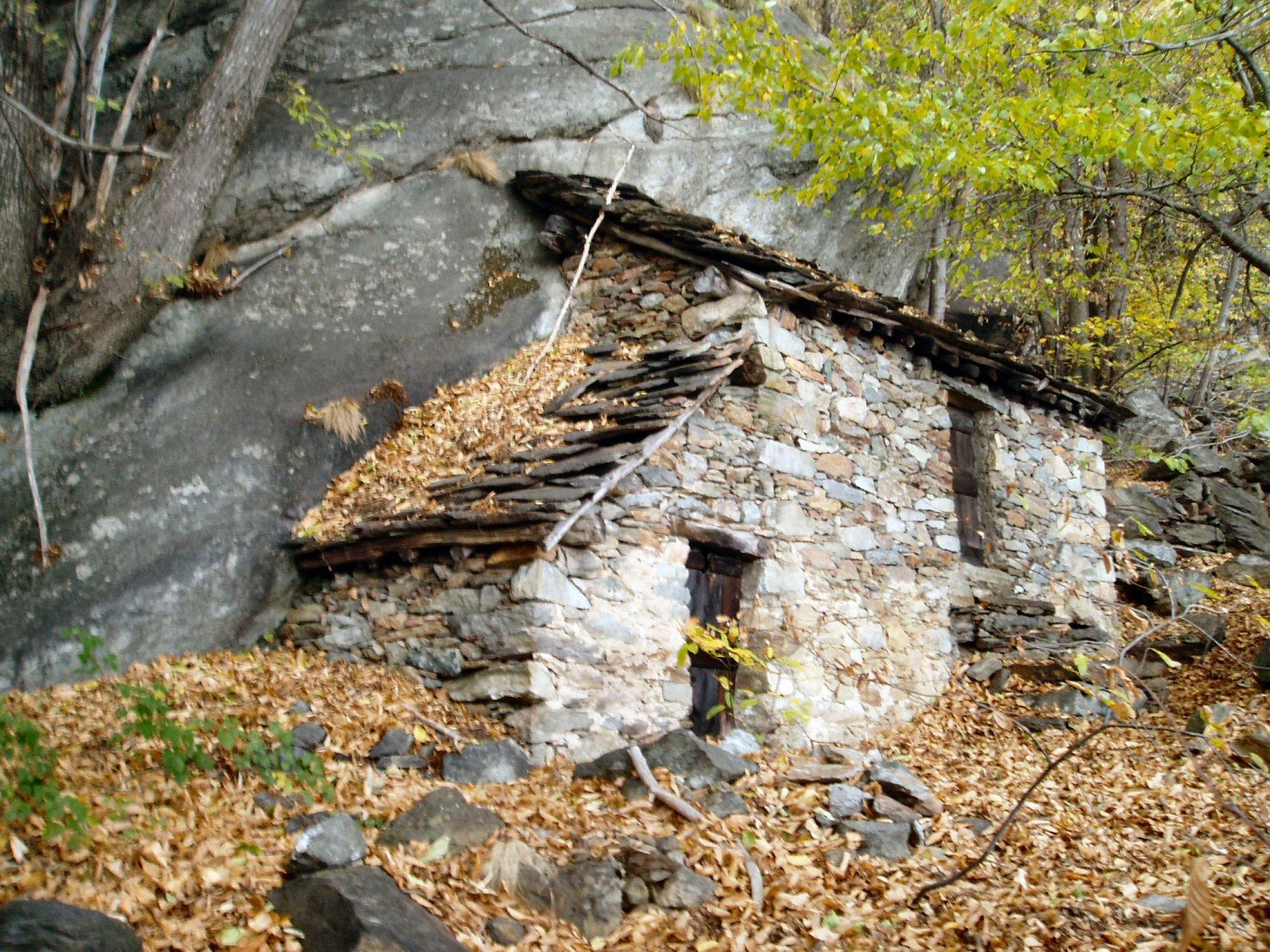 Casa addossata alla parete di roccia.