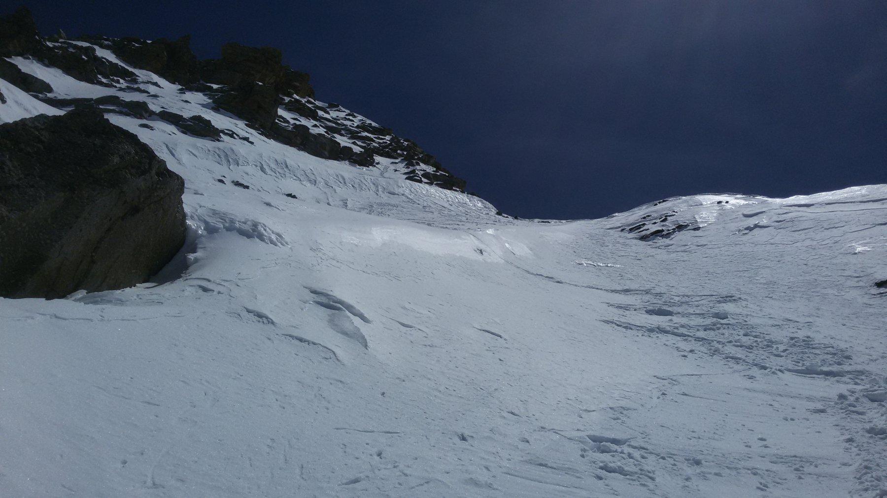 in discesa. la seconda parte dell'itinerario esposta a ovest: prima della parte di misto si vede il muretto di neve ripido e sopra ad esso l'inizio della traccia tra le rocce.
