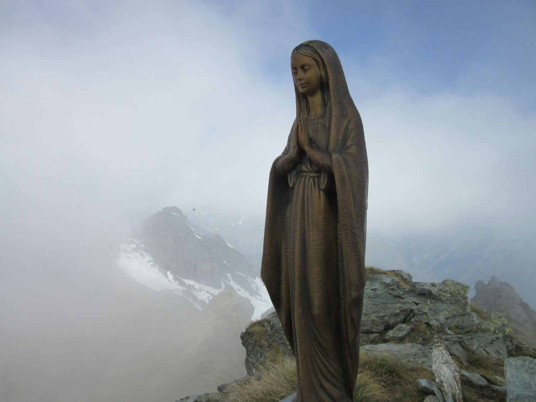 Madonnina sulla cima e dietro alle nuvole il Monte Rosa