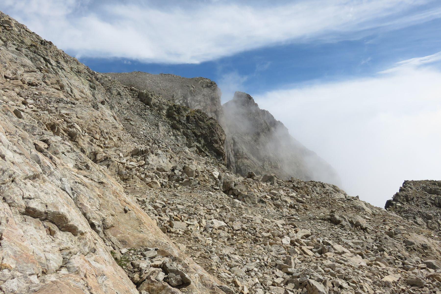 a dx, nella nebbia, la cima Asquasciati, vista dalla pietraia sotto la vetta del M. Clapier