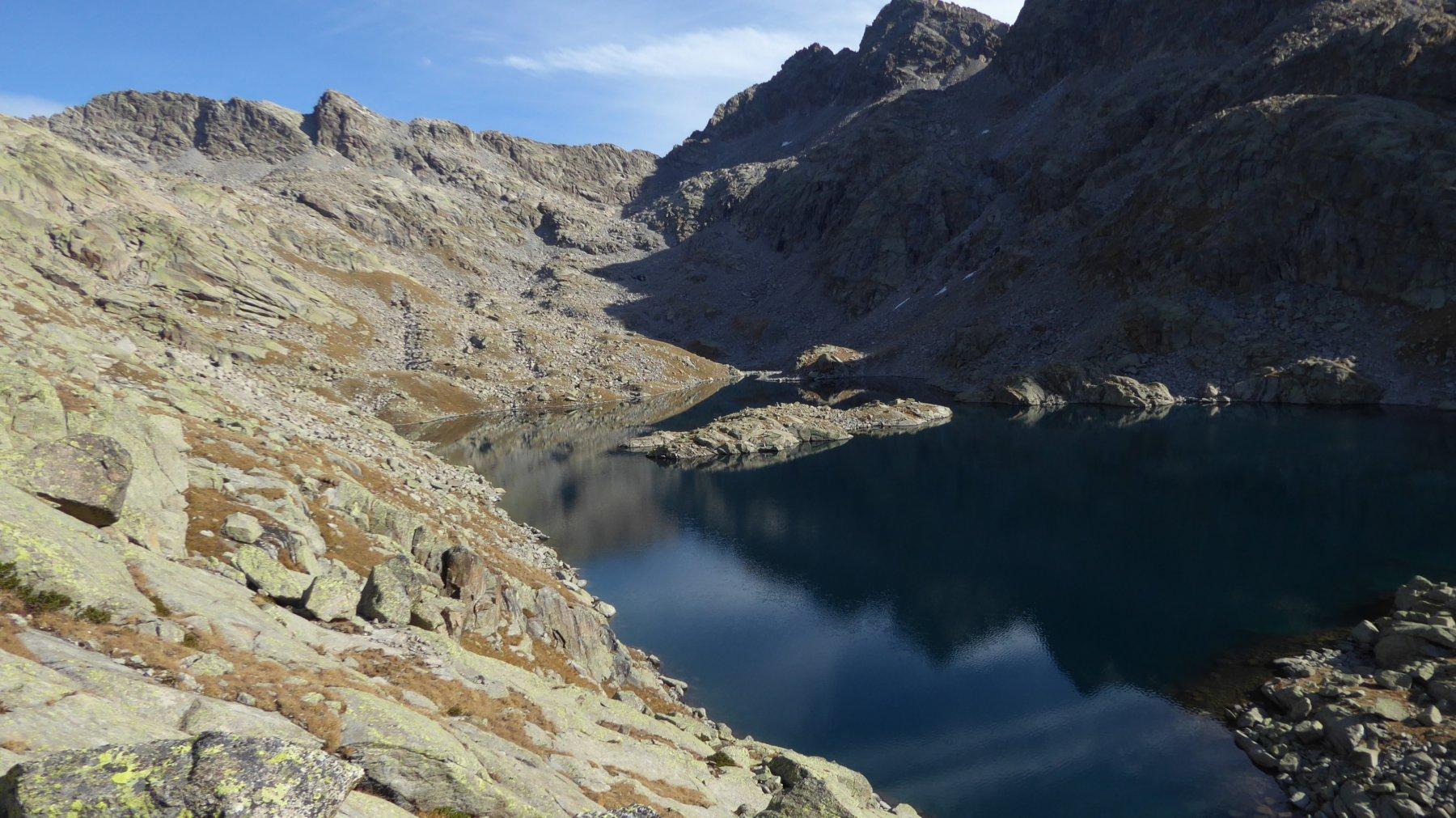 Lago della Motta ed in fondo, sul filo ombra-sole, la Bocchetta della Motta