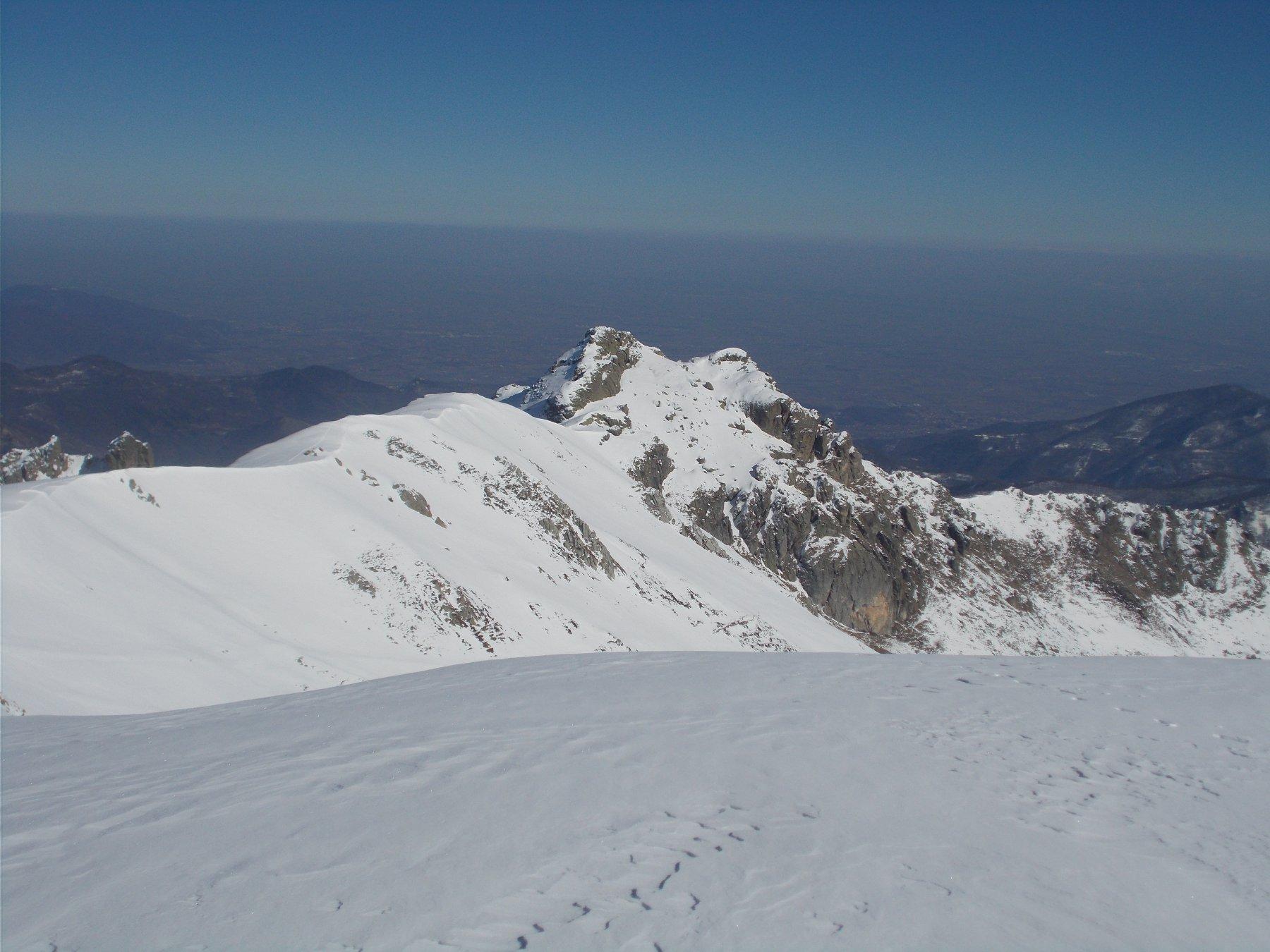 a est traspaiono al fondo della cresta le Rocce Pergo..