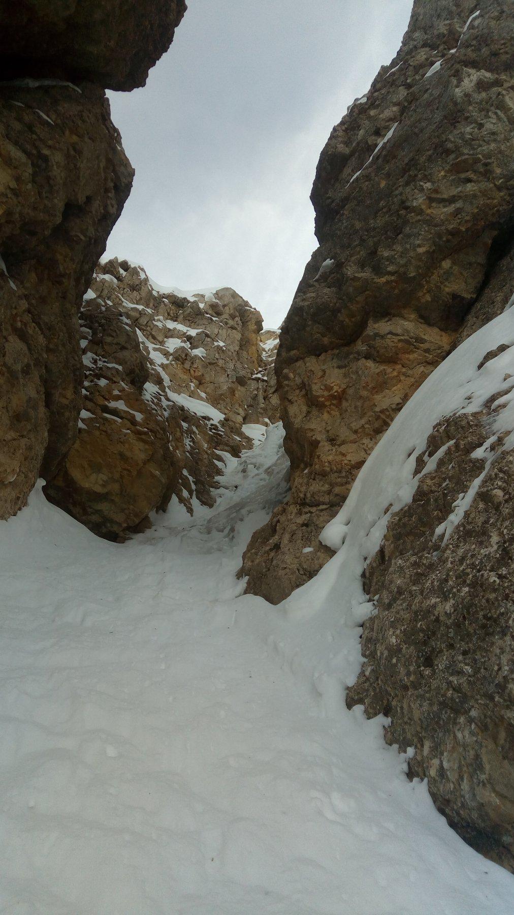 La strettoia-goulotte nascosta dietro le rocce, oltre la selletta nevosa al termine della rampa