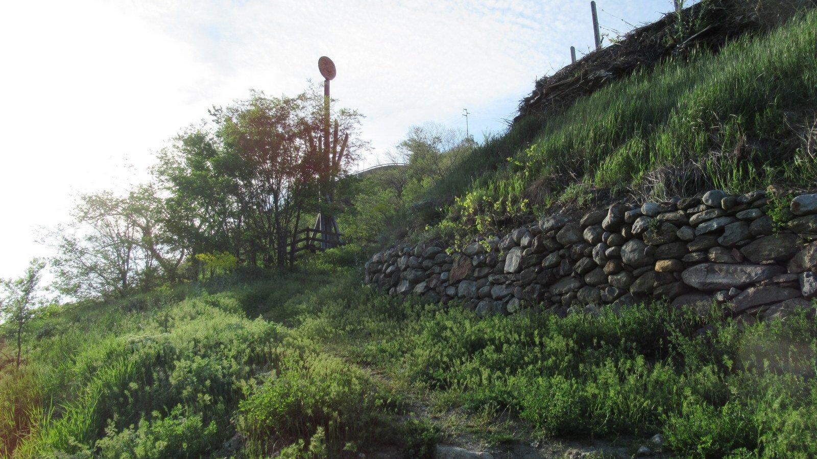 Il palo con il sole che ride a lato del sentiero che si imbocca dalla Francigena