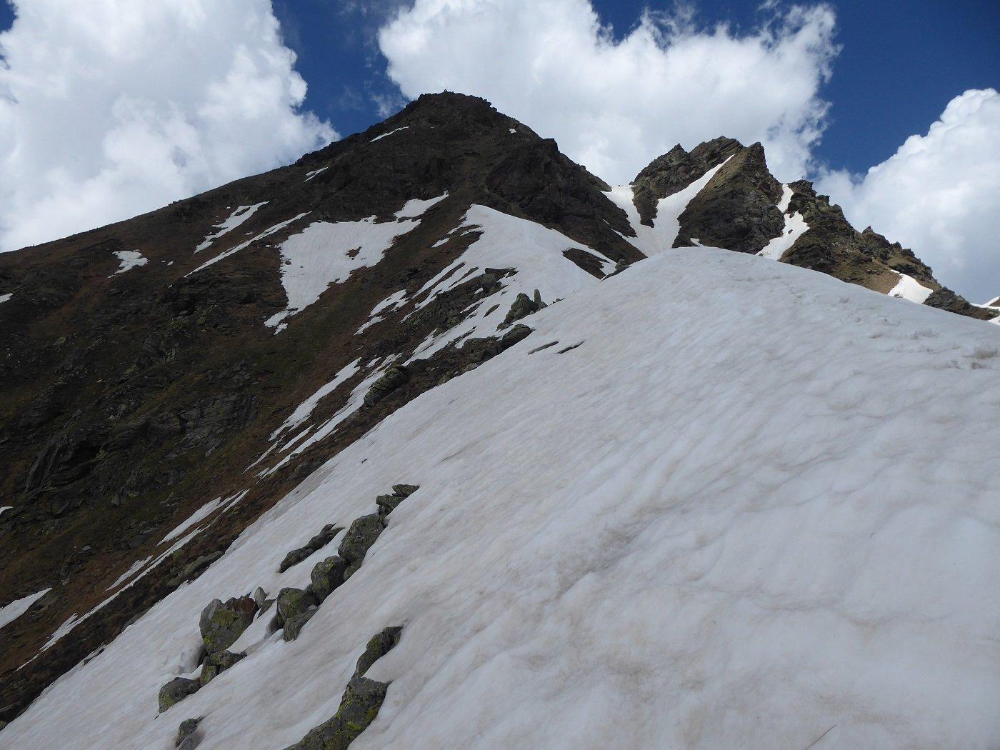 Sulla cresta finale. Si vedono a sinistra i nevai da attraversare per raggiungere la facile dorsale che porta in vetta.