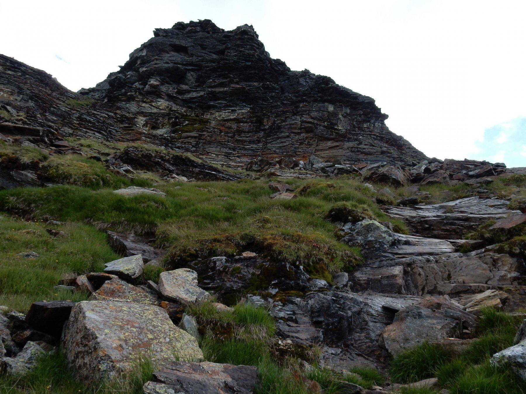 Un sentiero bollato di rosso porta sotto la bastionata rocciosa.