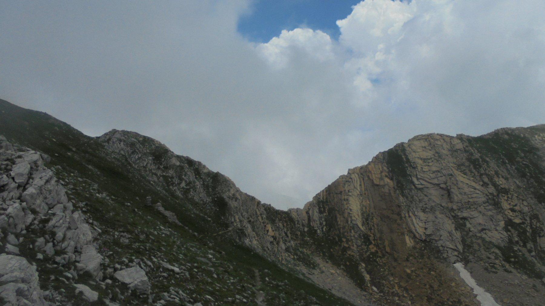 Verso l'intaglio del colle Palù, qualche tratto attrezzato con corde fisse. A sinistra Cima Bozano, a destra Palù