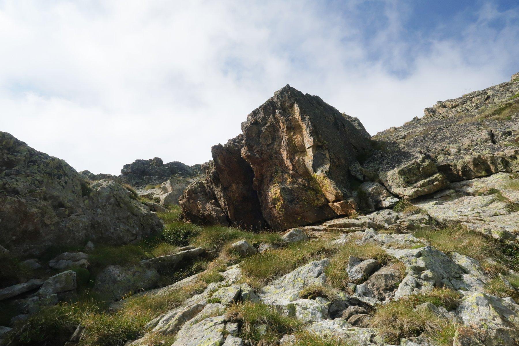 Il gobbone di roccia nera e arancione che è il primo punto di riferimento. Raggiungere la base erbosa poi salirci sopra da sinistra